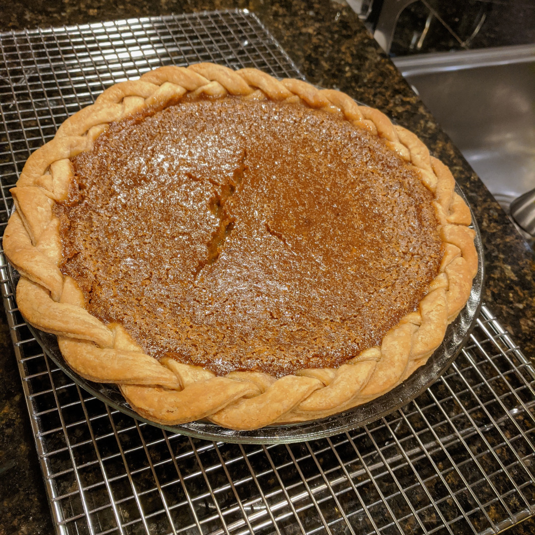 A pumpkin pie with braided crust and a cracked custard